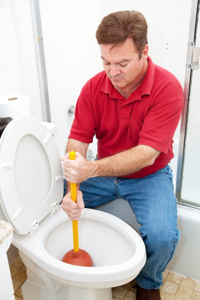plumber using a plunger to unclog a toilet