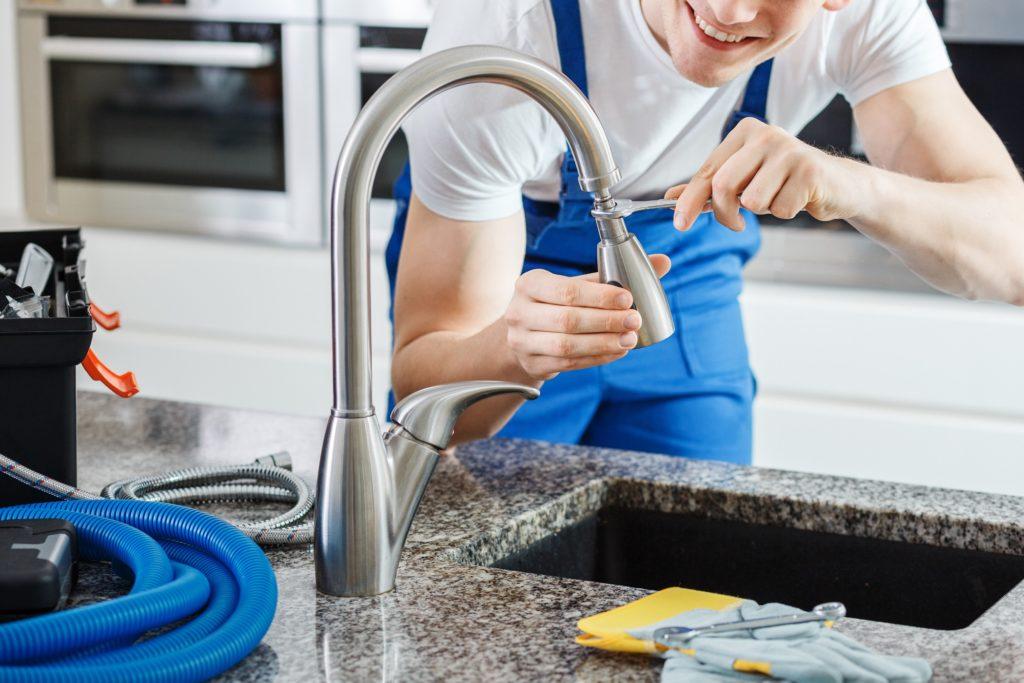 Smiling plumber fixing faucet