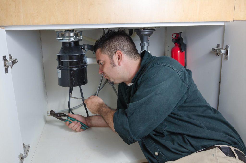 man fixing kitchen sink plumbing