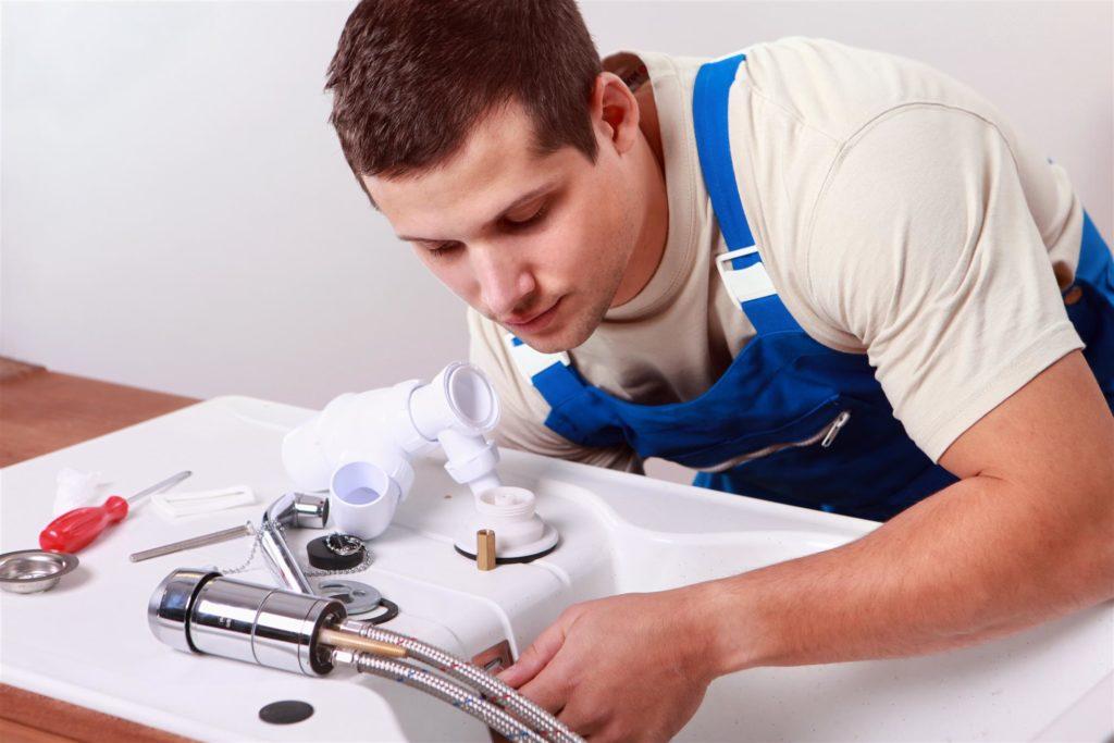 man fixing washing machine drain line