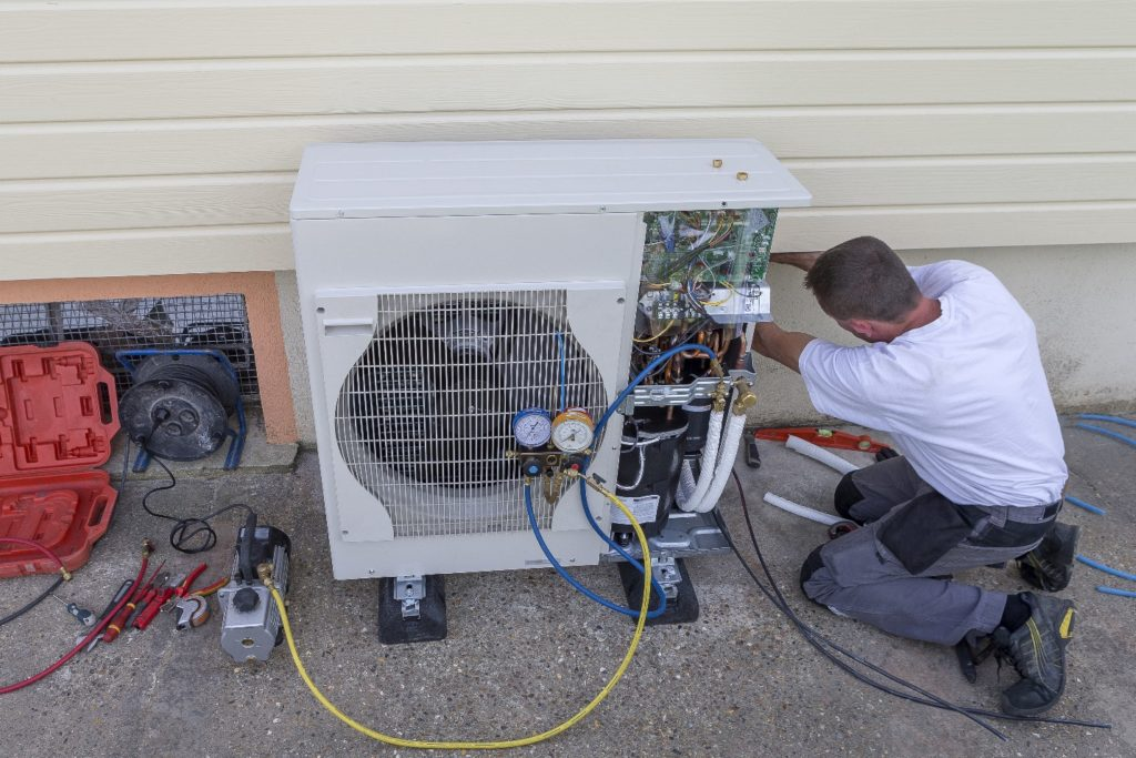 technician working on a heat pump outside