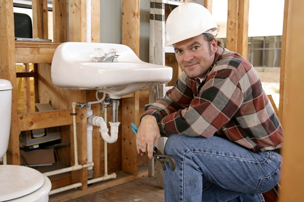 construction plumber installing bathroom fixtures