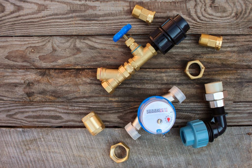 Plumbing equipment on wooden background.