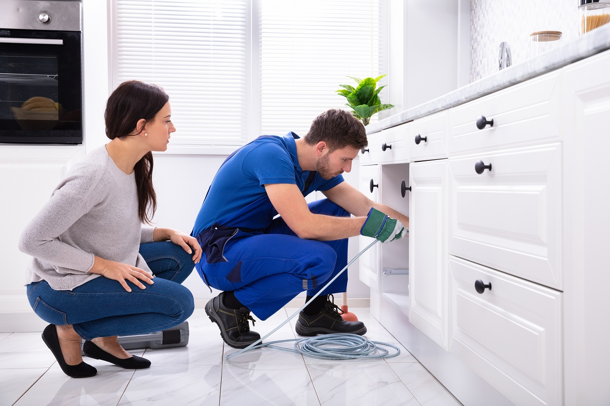Woman Looking At Male Plumber Cleaning Clogged Sink Pipe