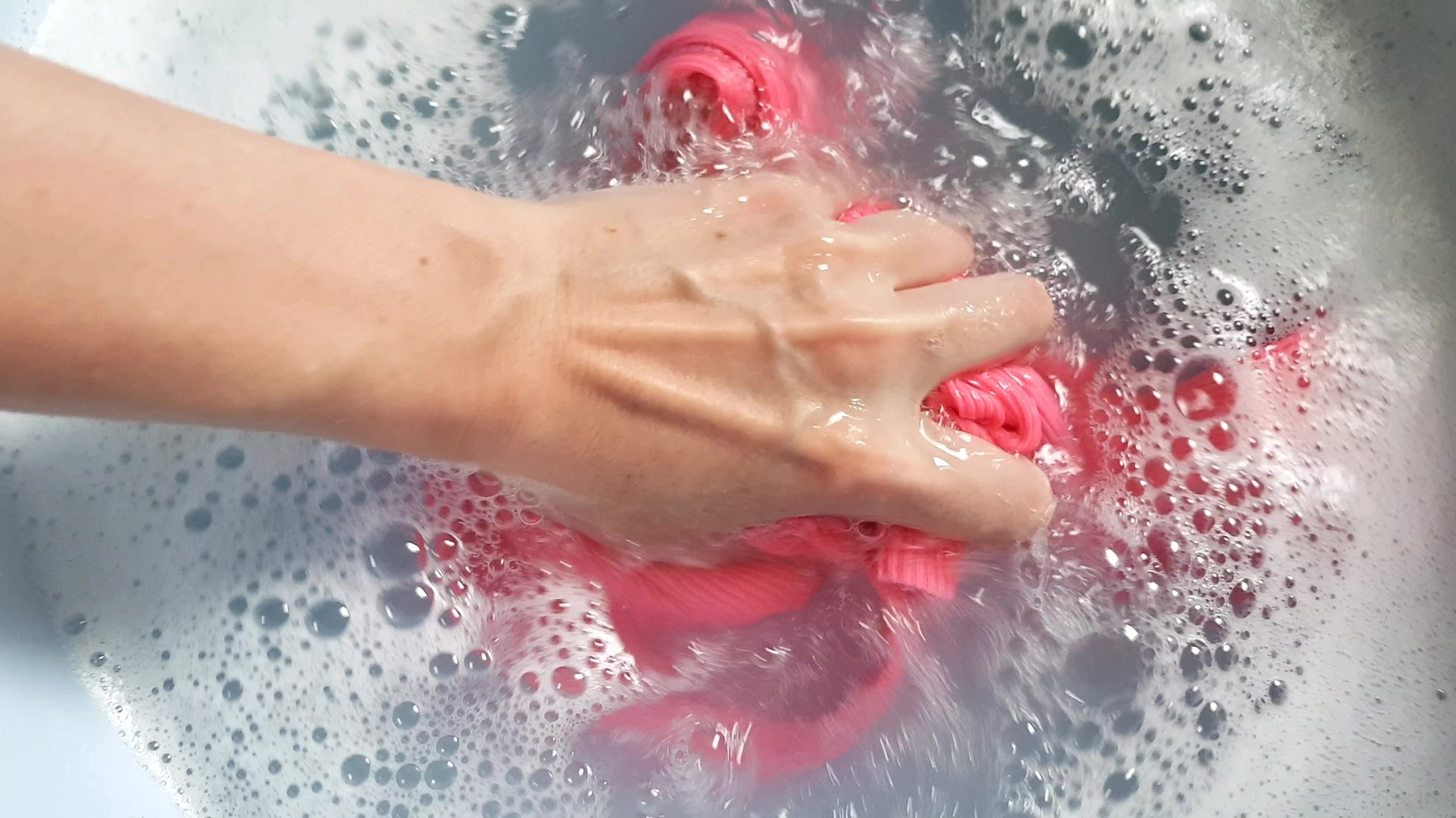 Female hand wash a pink T-shirt in a basin