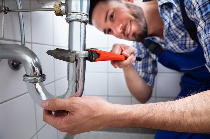 Plumber Repairing Sink With Adjustable Wrench
