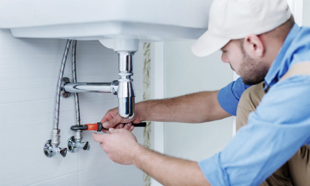 male plumber fixing a sink in bathroom