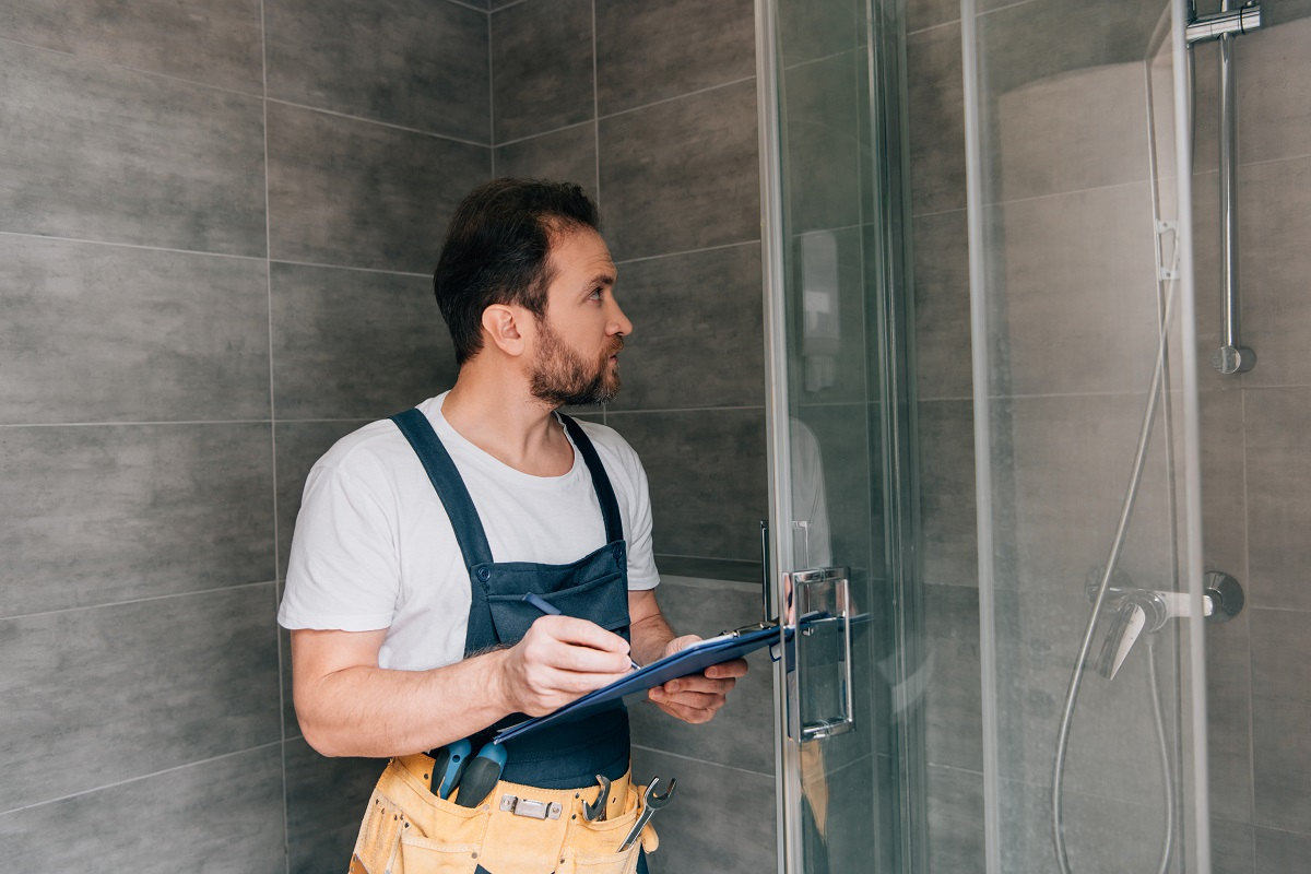 adult male plumber making notes in clipboard while checking shower in bathroom