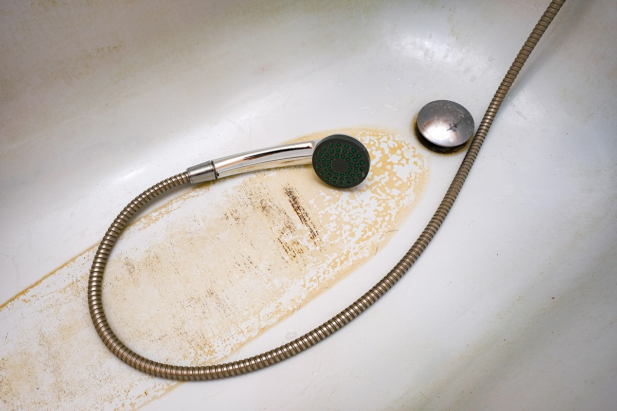 dirty bath drain mesh, hole and surface covered with limescale