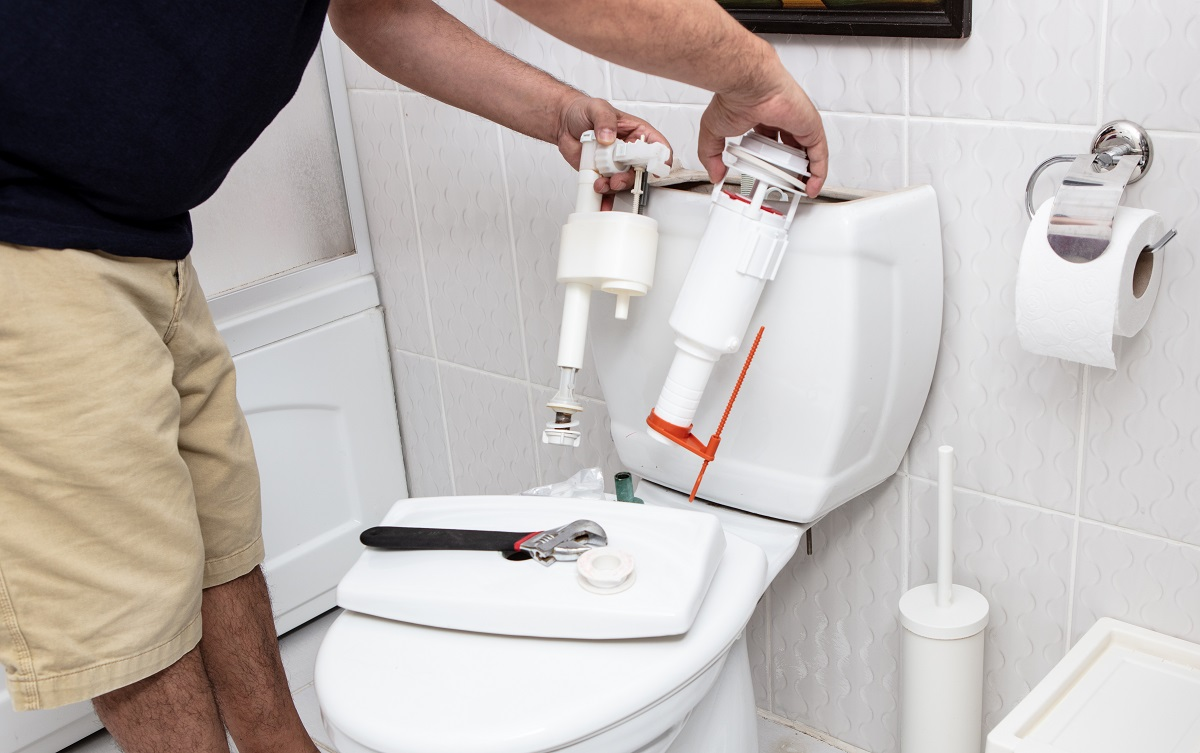 Man using tools repairing reservoir in a bathroom