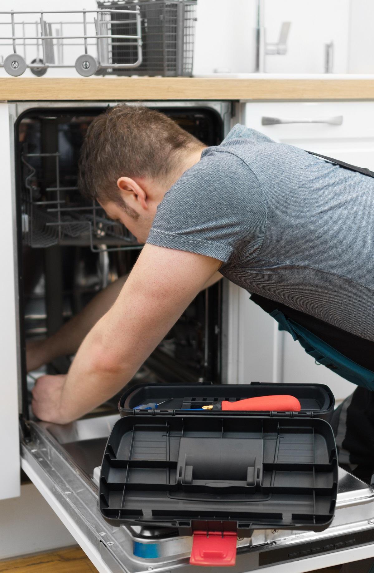 Professional handyman repairing dishwasher in the kitchen