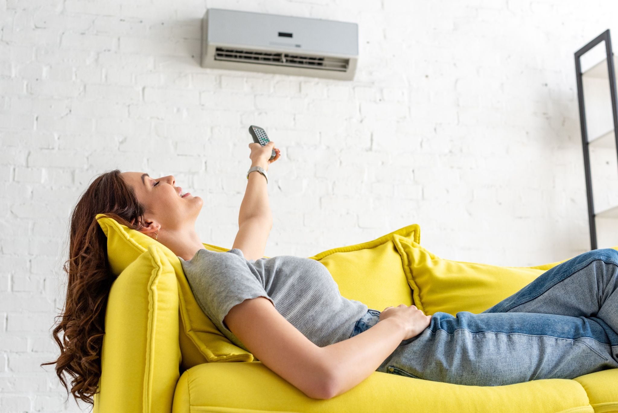 young woman relaxing under air conditioner and holding remote control