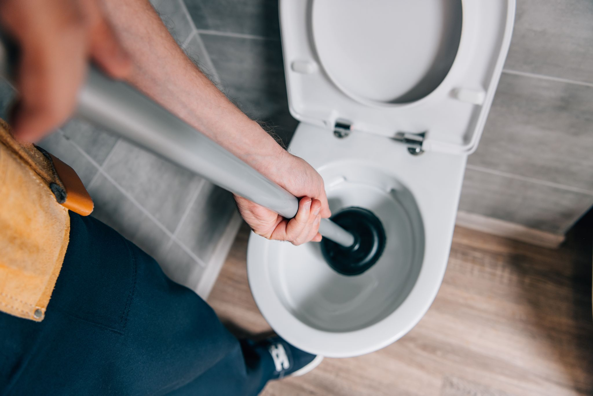 male plumber using plunger and cleaning toilet in bathroom