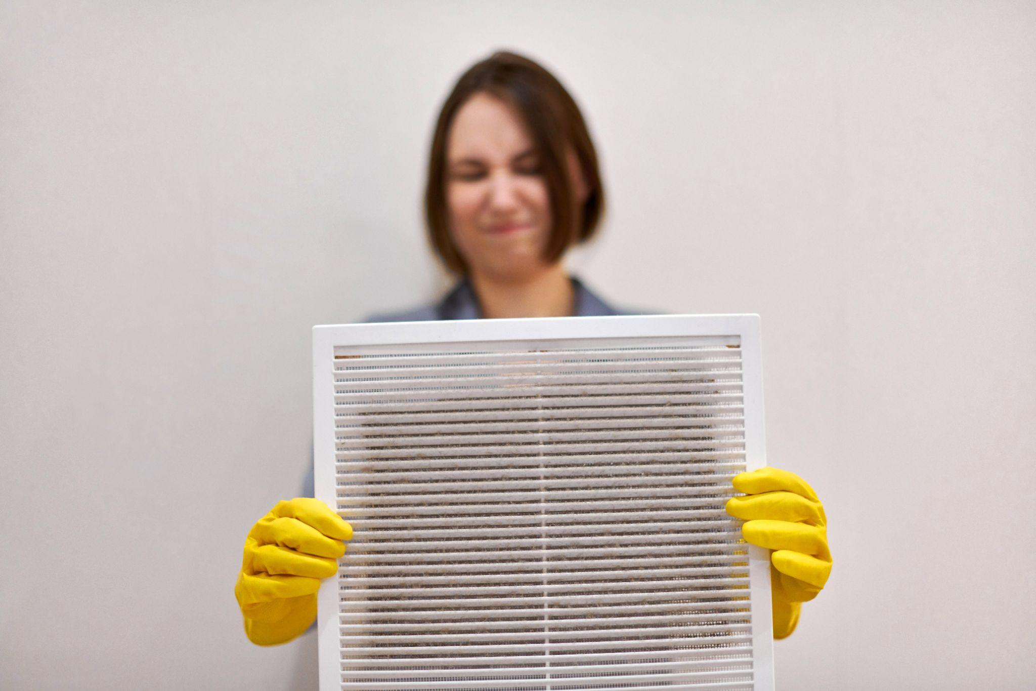 Woman holds ventilation grill with dust filter to clean it